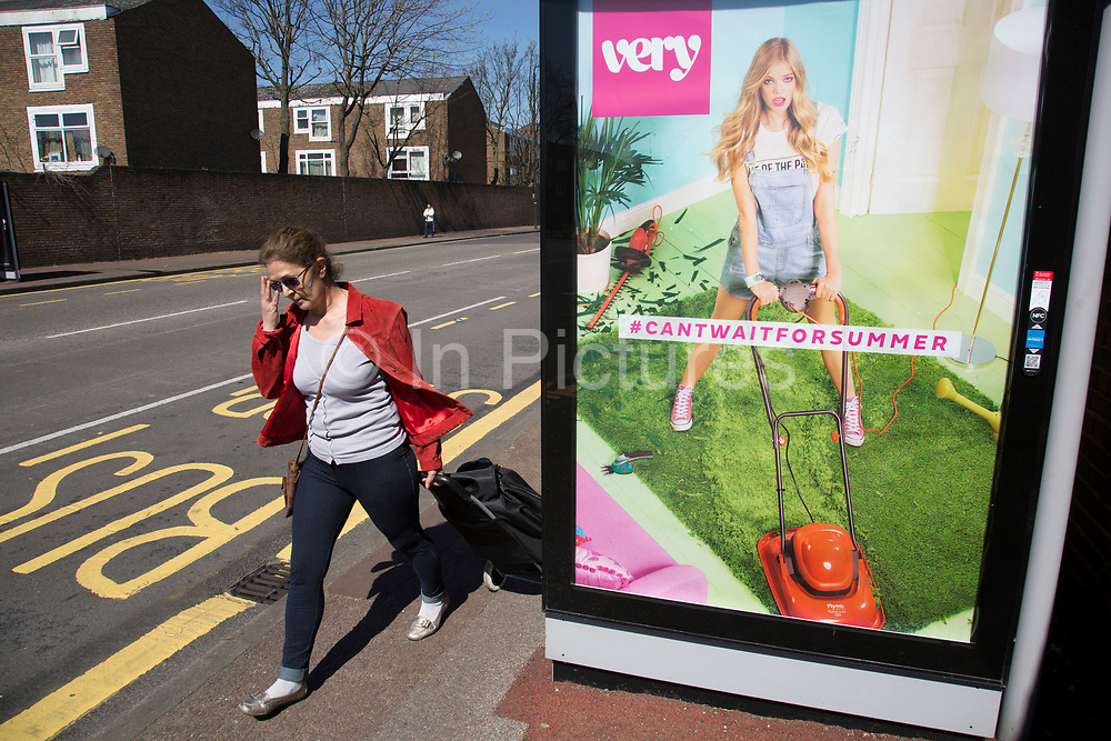 Woman striding past a bus shelter advert for retail clothes shop Very. Newham, East London, UK. The advertisement depicts a young girl wearing dungarees mowing her grass with a flymo lawn mower, with the tag line 'cant wait fro summer'.