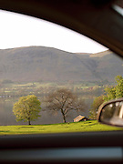 The countryside around a tree lined lake at Ullswater, Lake District, UK