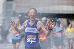 © Licensed to London News Pictures. 24/04/2016. London, UK. Runners in the Virgin Money London Marathon passing through a roadside shower near mile 23. Photo credit : Stephen Chung/LNP