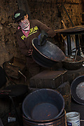 An indigenous Purepecha worker checks a copper pan for defects at a copper workshop in Santa Clara del Cobre, Michoacan, Mexico. The Purepecha people have been crafting copper crafts since the 12th century.