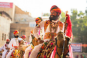 Parading on the backs of camels, Rajasthani men in traditional costumes at the Desert Festival on 29th January  in Jaisalmer, Rajasthan, India. It is an annual event that take place in February month in the beautiful city Jaisalmer. It is held in the Hindu month of Magh February, three days prior to the full moon. The men flaunt their moustaches, which go well with the Rajputana spirit that symbolizes the valor and glory of Rajasthan.