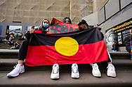 Three women hold an Aboriginal Flag on the steps of Parliament House during a Black Lives Mater rally on 06 June, 2020 in Melbourne, Australia. This event was organised to rally against aboriginal deaths in custody in Australia as well as in unity with protests across the United States following the killing of an unarmed black man George Floyd at the hands of a police officer in Minneapolis, Minnesota. (Photo by Dave Hewison/ Speed Media)