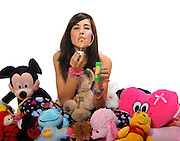 Young teen blows soap bubbles while surrounded by stuffed toys