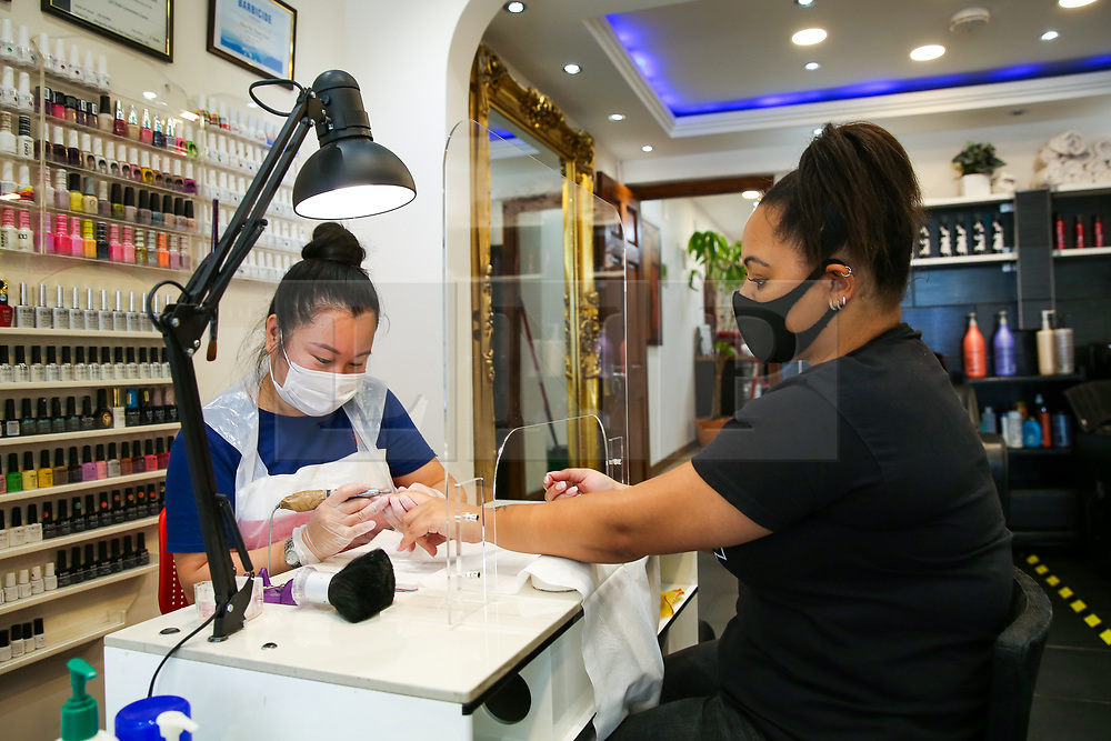 © Licensed to London News Pictures. 13/07/2020. London, UK. Nail beautician, HIEN THI THANH TRAN polishes KRISTINA'S nails in her salon in North London. Nail technicians and nail salons across the UK closed on 23 March following the coronavirus lockdown. As COVID-19 lockdown restrictions are eased, nail salons reopen today. Nail technicians and their clients are required to wear face coverings. Photo credit: Dinendra Haria/LNP