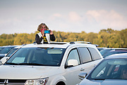 12 SEPTEMBER 2020 - DES MOINES, IOWA: A woman stands in the moonroof of her car during the Polk County Democrats Steak Fry at Waterworks Park in Des Moines. The Steak Fry is the largest fundraiser of the year for Polk County Democrats. This year nearly 1,000 people attended. The Steak Fry observed public health guidelines. Normally the Steak Fry is a picnic but this year people stayed in their cars while meals were brought to them and they wore masks when they were outside of the cars. Most of the speakers appeared via online speeches.   PHOTO BY JACK KURTZ
