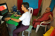 """Photographer editing a monk's passport photo with photoshop. Monks are expected to provide a living example for the laity and to serve as a """"field of merit"""" for lay followers."""