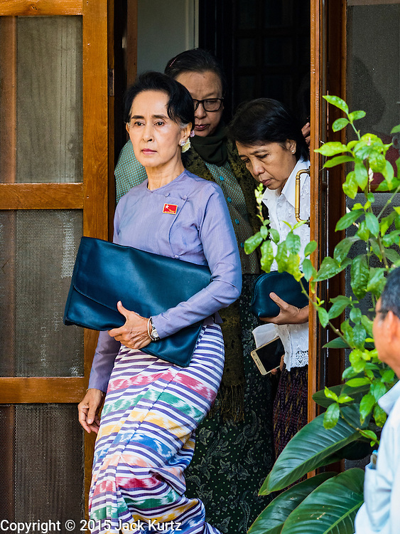 """05 NOVEMBER 2015 - YANGON, MYANMAR: AUNG SAN SUU KYI leaves her home and walks to the press conference in her garden. During the press conference, which lasted 90 minutes, Aung San Suu Kyi, the leader of the National League for Democracy (NLD), said that if the NLD won the election she would serve """"above"""" the President. When questioned about the Rohingya crisis in western Myanmar, a reporter called the situation """"dramatic"""" and Suu Kyi replied the entire country is in a """"dramatic situation"""" and the problems of the Rohingya should not be """"exaggerated."""" She said the """"great majority of our people remain as poor as ever."""" She also said the NLD would make a """"fuss"""" if election results were """"suspicious."""" Citizens of Myanmar go to the polls Sunday November 8 in what is widely viewed as the most democratic and contested election in Myanmar's history. The NLD is widely expected to win the election.   PHOTO BY JACK KURTZ"""