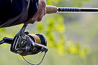 An angler using a spin fishing reel.
