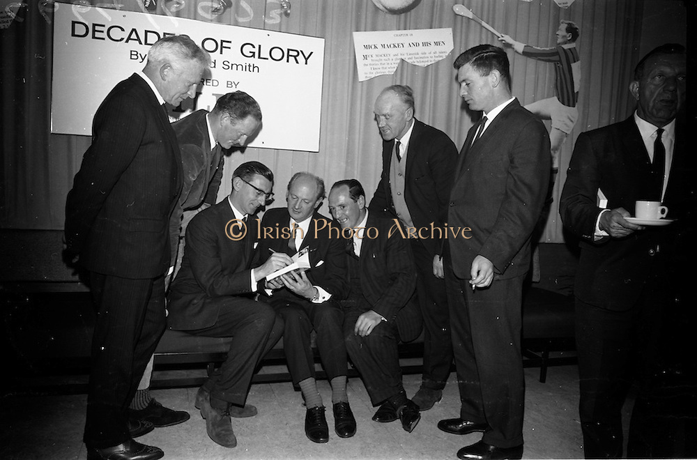 "17/05/1966<br /> 05/17/1966<br /> 17 May 1966<br /> Book reception for ""Decades of Glory: A Comprehensive History of the National Game"" by Raymond Smith.<br /> This reception was held in the offices of W.D. & H.O. Wills to honour the well known author and journalist, Raymond Smith. His book on the history of Hurling (""Decades of Glory"") has just been published with the assistance of Wills of Dublin and Cork and the Central Council of the G.A.A.<br /> Picture shows (from left to right): Sean Duggan (Galway), Billy Rackard (Wexford),  Raymond Smith (autographing his book), Mr. Jack Lynch (at the time he was Minister for Finance), Jimmy Langton (Kilkenny), John Keane (Waterford), and Jimmy Smith (Clare)."