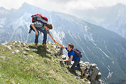 Teenage boys helping friend climbing in mountains