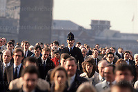 A tall City of London police officer seen amongst the rush hour commuters  as they walk over London Bridge. Photograph by Terry Fincher