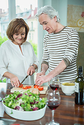 Couple preparing food in kitchen, smiling