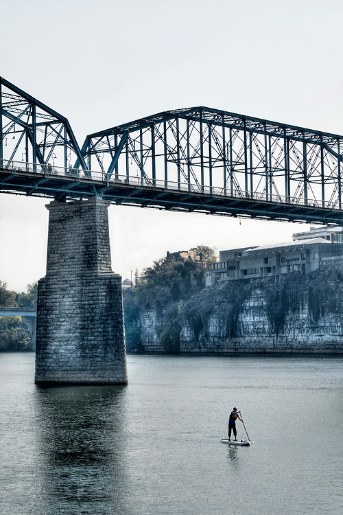 A single paddleboarder floats down the Tennessee River beneath the Walnut Street Bridge in Chattanooga, TN on Saturday, November 12, 2016. Copyright 2016 Jason Barnette