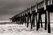 Hurricane force winds send waves crashing into the pier at Pensacola Beach, Florida