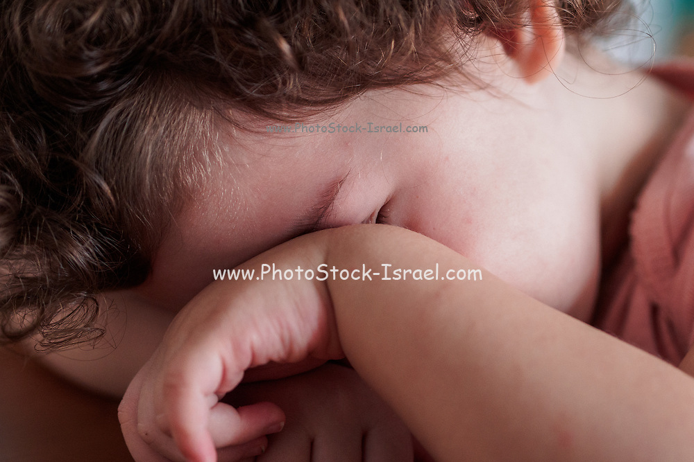 Bashful toddler hides her face behind her hand