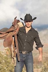 All American cowboy outdoors with a saddle All American cowboy carrying a saddle on a mountain range