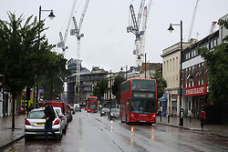 6 June 2017 - Demolition of White Hart Lane<br /> London red buses make their way down Tottenham High Road with the new build of White Hart Lane in the background<br /> Photo: Mark Leech