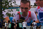 Team GB men's lightweight four rowers interviewed on large TV screen during the London 2012 Olympics. Juxtaposed with two dispensing workers of expensive beer, one of the British silver medallist rowers from the rowers seems to have a thirst for alcohol after a tight finish and spectators pass by. This land was transformed to become a 2.5 Sq Km sporting complex, once industrial businesses and now the venue of eight venues including the main arena, Aquatics Centre and Velodrome plus the athletes' Olympic Village. After the Olympics, the park is to be known as Queen Elizabeth Olympic Park.