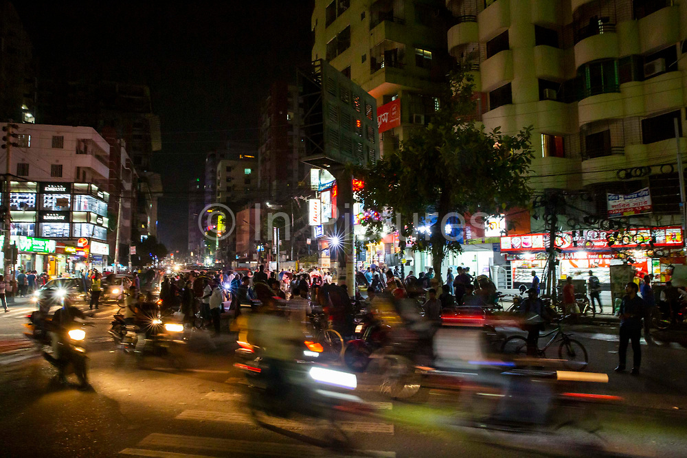 Scooters and cars driving along the busy Shanti Nagar road at night on the 23rd of September 2018 in Dhaka, Bangladesh.