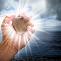 Holding a heart shaped rock against stormy skies. The heart rock is radiating light to guide the way through the troubled relationship.