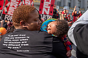 """San Francisco, USA. 19th January, 2019. The Women's March San Francisco begins with a rally at Civic Center Plaza in front of City Hall. A woman smiles at the baby sleeping on her shoulder, and on the back of her black T-shirt is the quote from Audre Lorde reads: """"I am not free while any woman is unfree, even when her shackles are very different from my own."""" Matching T-shirts were worn by many women and LGBTQ representatives from the Young Women's Freedom Center attending the rally and march. Credit: Shelly Rivoli/Alamy Live News"""