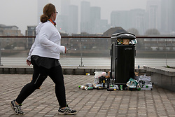 © Licensed to London News Pictures. 01/04/2021. London, UK. A woman walks past an overflowing bin in Cutty sark Gardens after large groups of people visited to enjoy the warm weather and take advantage of new lockdown rules that allow groups of six to meet outside. Photo credit: George Cracknell Wright/LNP