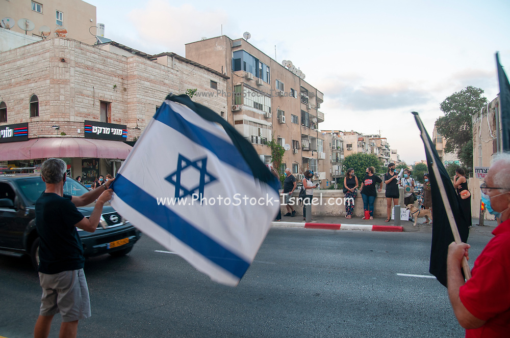 Thousands of nationwide 'Black flag' activists protest against Binyamin (Bibi) Netanyahu who is facing 3 charges of corruption in Israeli courts. The protesters claim that a corrupt person is not suitable to be prime minister. Netanyahu (AKA Crime Minister) is doing all he can to hold on to his post and delay his day in court including using the Current global Pandemic to fight for his personal survival. Photographed on Yefet street in Jaffa, Israel on July 25 2020