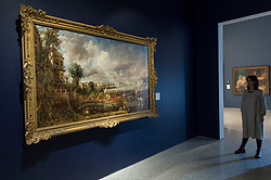 "© Licensed to London News Pictures. 11/01/2019. LONDON, UK. A staff member views ""The Opening of Waterloo Bridge ('Whitehall Stairs, June 18th, 1817')"" by John Constable.  The painting is being shown with ""Helvoetsluys"", 1832, by J.M.W. Turner (R) at The Royal Academy of Arts in Piccadilly for the first time since the artists clashed at the Summer Exhibition in 1832.  Turner allegedly added a small dab of red paint to his canvas, which he then converted into an image of a buoy floating in the sea. when he saw his painting next to Constable's.  The two works form ""He has been here and fired a gun"": Turner, Constable and the Royal Academy, on display from 12 January to 31 March 2019.  Photo credit: Stephen Chung/LNP"