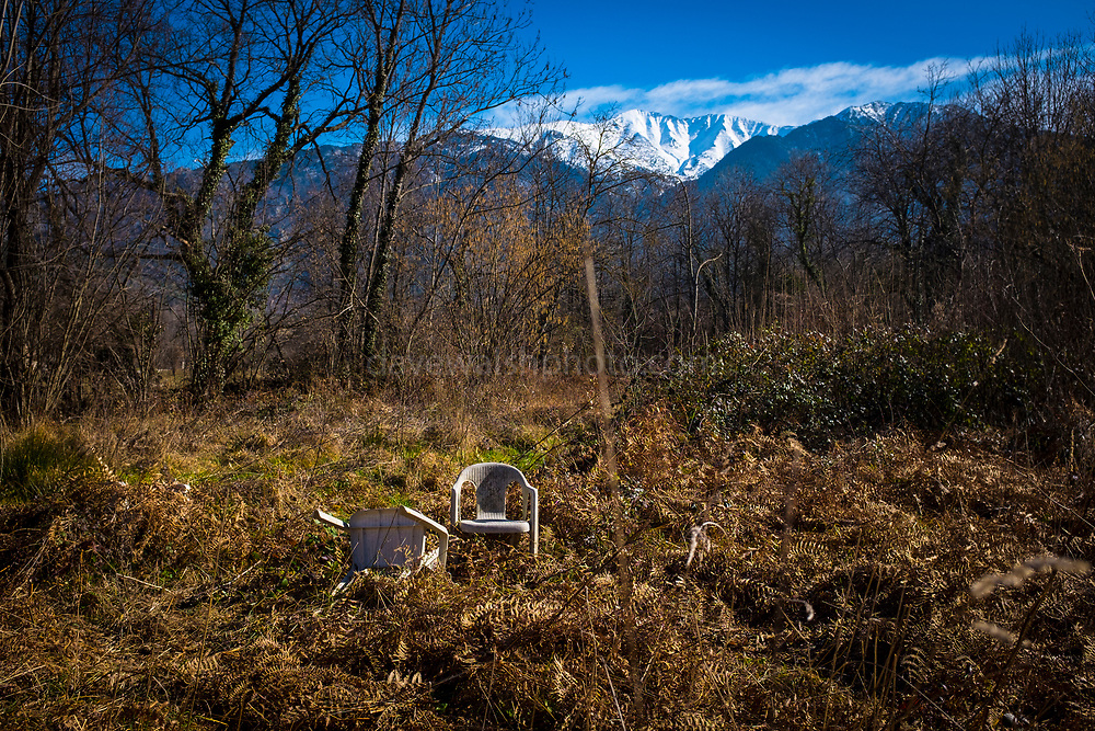 Abandoned plastic chairs beneath a mountain, France