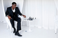 Young African American Playing Chess in a upscale location.