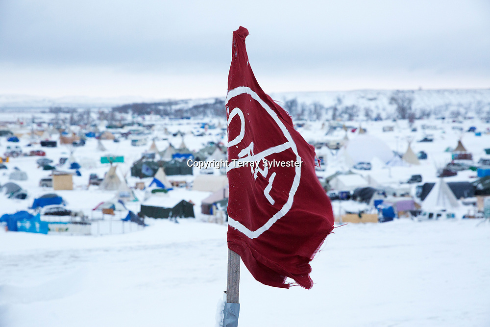 A flag flies over the opposition camp against the Dakota Access oil pipeline on November 30, 2016. Cannon Ball, North Dakota, United States.