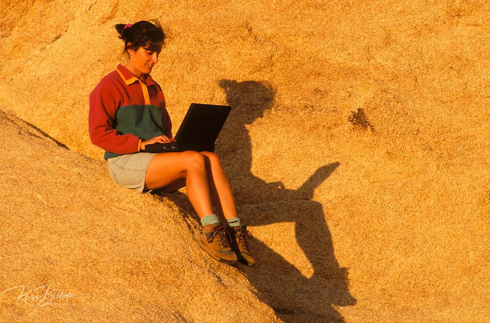 Warm evening light on woman sitting on boulder using a laptop computer, Joshua Tree National Park, California