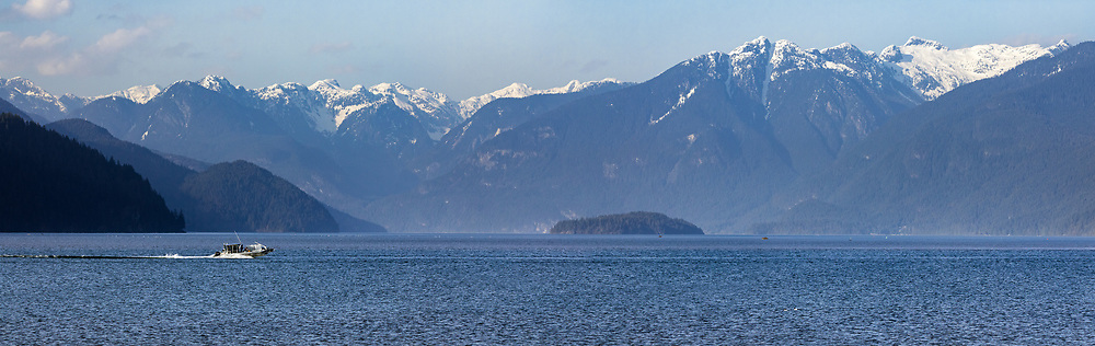 A boat heads up Pitt Lake with Osprey Mountain (right) and other peaks from the Garabaldi Ranges in the background.  Photographed from the Katzie Loop trail in Pitt Meadows, British Columbia, Canada.