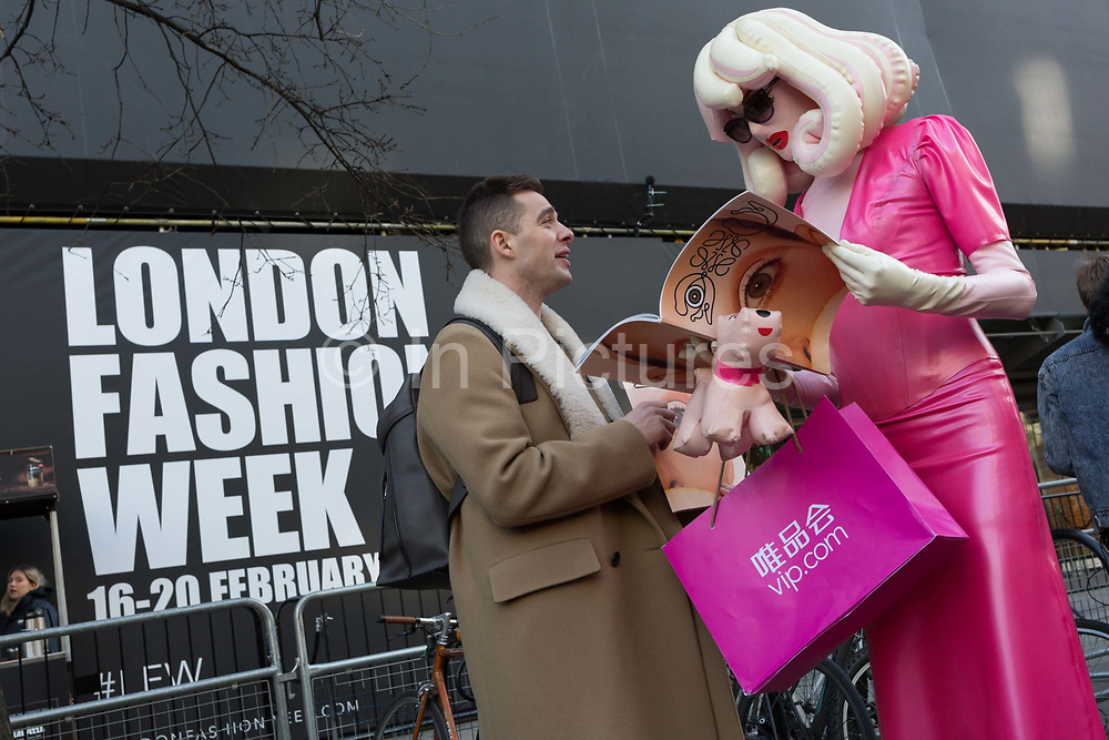 The fine art character known as Pandemonia part parody and living is handed a free magazine featuring a models eye on the cover on the first day of London Fashion Week, in the Strand, on 16th february 2018, in London, England. Pandemonia states  that she is a 7ft tall personality often seen at exclusive premiers, events and exhibitions. Post pop, conceptual artist, written about in iD, independent and Vogue publications. Otherwise, few have any idea about who or what this cartoon character is, or even how this creature secures an invite to parties, society and art events. The writer Poonperm Paitayawat says .. She is about branding, self-image and lifestyle. She is tapping into the collective unconsciousness. Pandemonia goes beyond pop art.