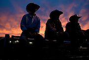 From left, Brady Pitchford, Landon Cornia and Kade Pitchford watch the Jackson Hole Rodeo as the last rays of daylight throw rich colors across the sky.