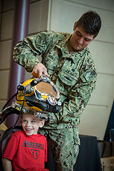 MILWAUKEE (Aug. 6, 2018) Navy Diver 1st Class Thomas Gerace, assigned to Explosive Ordnance Disposal Group (EODGRU) 2, places a KM-37 diving helmet on a volunteer at the Milwaukee Public Museum during Milwaukee Navy Week. The Navy Office of Community Outreach uses the Navy Week program to bring Navy Sailors, equipment and displays to approximately 14 American cities each year for a week-long schedule of outreach engagements designed for Americans to experience firsthand how the U.S. Navy is the Navy the nation needs. (U.S. Navy photo by Mass Communication Specialist 1st Class Ryan J. Batchelder/Released)180806-N-EH218-0100