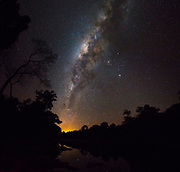 The Milky Way seen from Brazilian rainforest along the shore of Rio Cristalino, southern Amazon. Mosaic of 2 images. The orange glow is the lights from the city of Alta Floresta. Mars and Saturn together with the orange star Antares form the triangle just to the right (north) of the galactic centre.