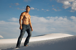 sexy shirtless muscular man in jeans walking on a sand dune