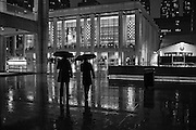 Two men with umbrellas crossing the Josie Robertson Plaza at Lincoln Center on a rainy December night.