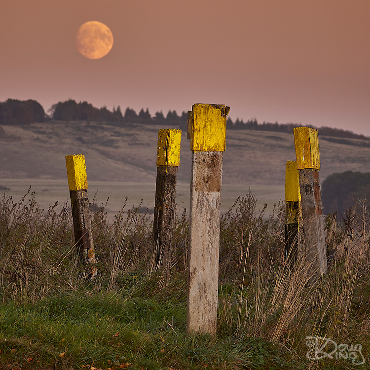 The full moon rises over the weathered wooden posts that mark Z Crossing on the British Army ranges on Salisbury Plain