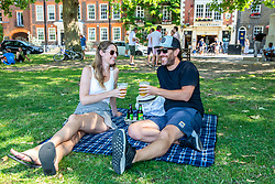 © Licensed to London News Pictures. 25/06/2020. London, UK. Helen Tukapua 34 and husband Reagan 41 from Chiswick cool off with a takeaway pint on Richmond Green in South West London as forecasters predict the hottest day of the year so far with temperatures expected to reach 33c. Prime Minister, Boris Johnson announces this week that tourism and hospitality, including pubs, restaurants and campsites can now reopen from the 4th of July as well as reducing the 2 metre rule to 1 metre. Photo credit: Alex Lentati/LNP