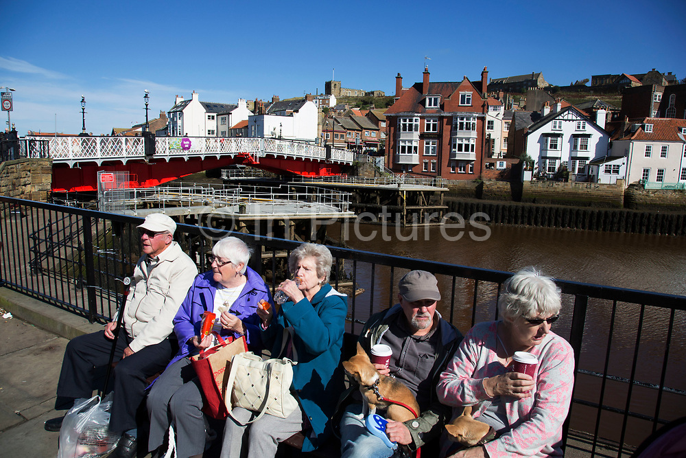 Tourists along the quayside at the harbour in Whitby, a seaside town, port in the county of North Yorkshire, originally the North Riding. Situated on the east coast at the mouth of the River Esk. Tourism started in Whitby during the Georgian period and developed. Its attraction as a tourist destination is enhanced by its proximity to the high ground of the North York Moors, its famous abbey, and by its association with the horror novel Dracula. Yorkshire, England, UK.