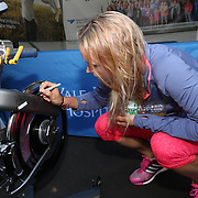 August 16, 2014, New Haven, CT:<br /> Caroline Wozniacki autographs a spin bike in the Yale New Haven Health booth during WTA All-Access Hour on day three of the 2014 Connecticut Open at the Yale University Tennis Center in New Haven, Connecticut Sunday, August 17, 2014.<br /> (Photo by Billie Weiss/Connecticut Open)
