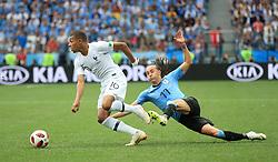 France's Kylian Mbappe (left) and Uruguay's Diego Laxalt battle for the ball