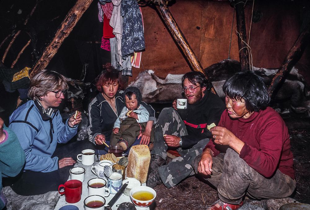 Nancy Shute and Afanassi Makovnev have a meal with Olga Tinachvanau and family in yrangra, Chukchi reindeer camp, Senyavina Strait, Chukotsk Peninsula, NE Russia, 1992