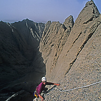 Mountaineer Mark Newcomb ascends treacherous conglomerate rock on Shipton's Arch in the arid Kara Tagh Mountains next to the Taklimakan Desert near Kashagar (Kashi) in Xinjiang Province, China.  Later the team crossed the range, descending into the dangerous and previously unknown slot canyon behind him.
