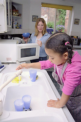 Young girl washing up plastic cups in kitchen sink with mother watching,