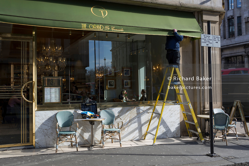While customers sit in winter sunlight, a workman stands on stepladders to repair the awning of Cafe Grand by Concerto on on the corner of Dover Street and Piccadilly, on 18th February 2020, in London, England.