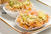 Group Avocado and Shrimp Volauvent in a serving tray. Volauvent is a tiny round canapé made of puff pastry. The term ' vol au vent ' means ' blown by the wind ' in French.
