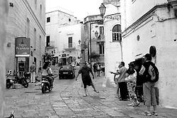 Davanti alla bottega di un rigattiere, un turista prova a schioccare con una frusta in vendita, seguendo i consigli del venditore, senza riuscirci.